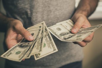 A man in a gray T-shirt holds dollars in his hands.