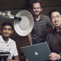 three men posed around a robotic arm holding a plate