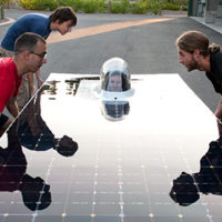 People lifting a solar panel.