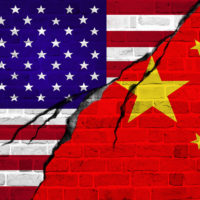 illustration of a crack in a brick wall painted with US and China flags