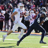 Stanford football player rinning with the ball with an opponent tries to head him off.