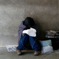 homeless person huddled in a subway station