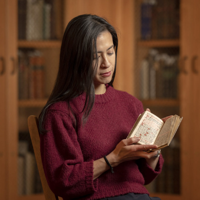 Marisa Galvez holds a contemplative manuscript from the 16th century made for a Franciscan nun