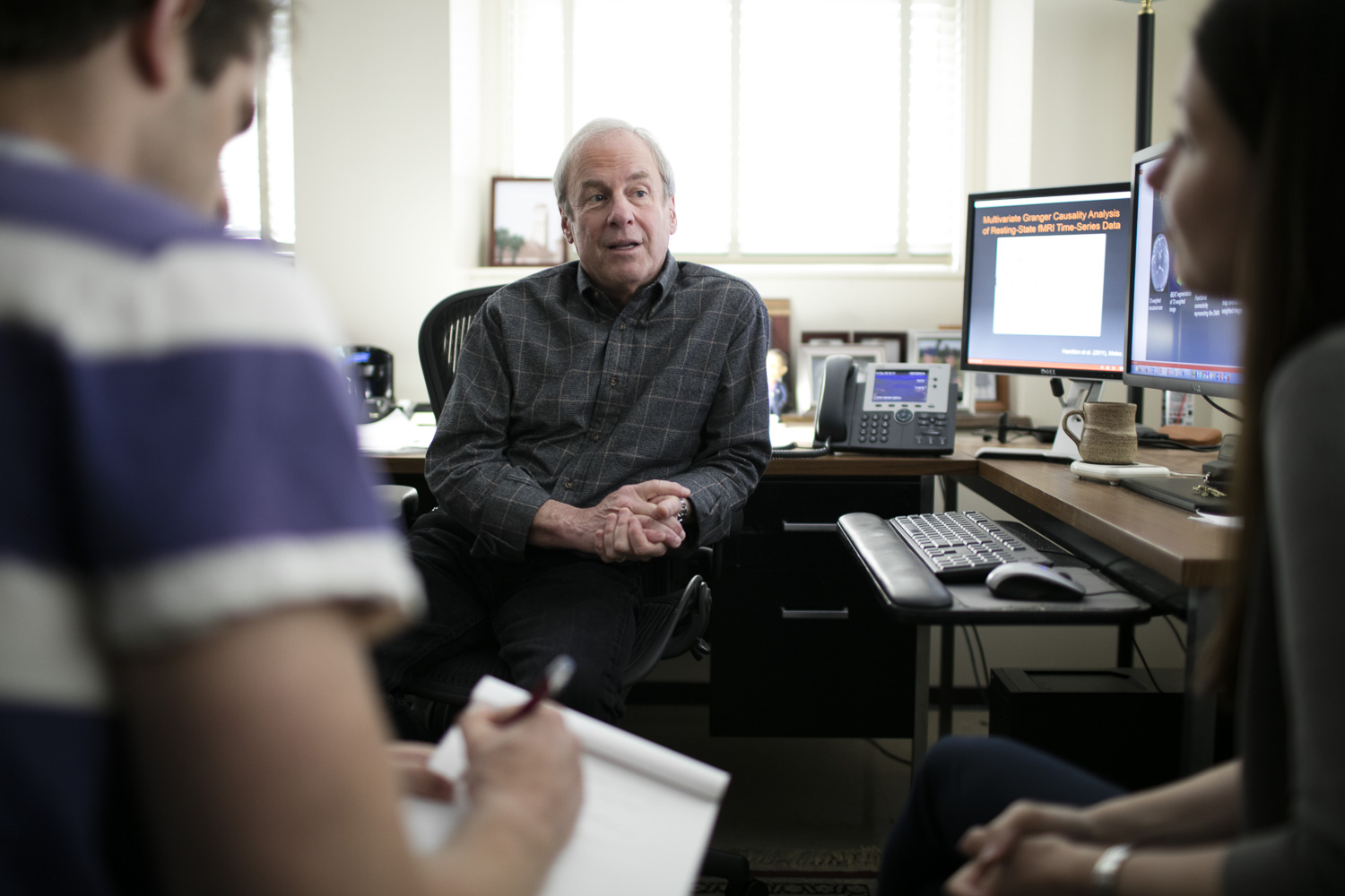Psychology professor Ian Gotlib confers with students in his office.