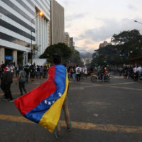 protestor wearing Venezuelan flag as a cape
