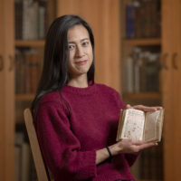 Marisa Galvez, holds a manuscript from Stanford Libraries Special Collections