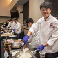 "Kevin Guo, '22, of Team Three prepares ""ooo-baby pork chops"" at the 16th annual Cardinal Cook-Off on Jan. 24 at the Arrillaga Family Dining Commons."
