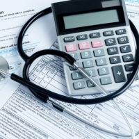 Calculator and stethoscope on paperwork