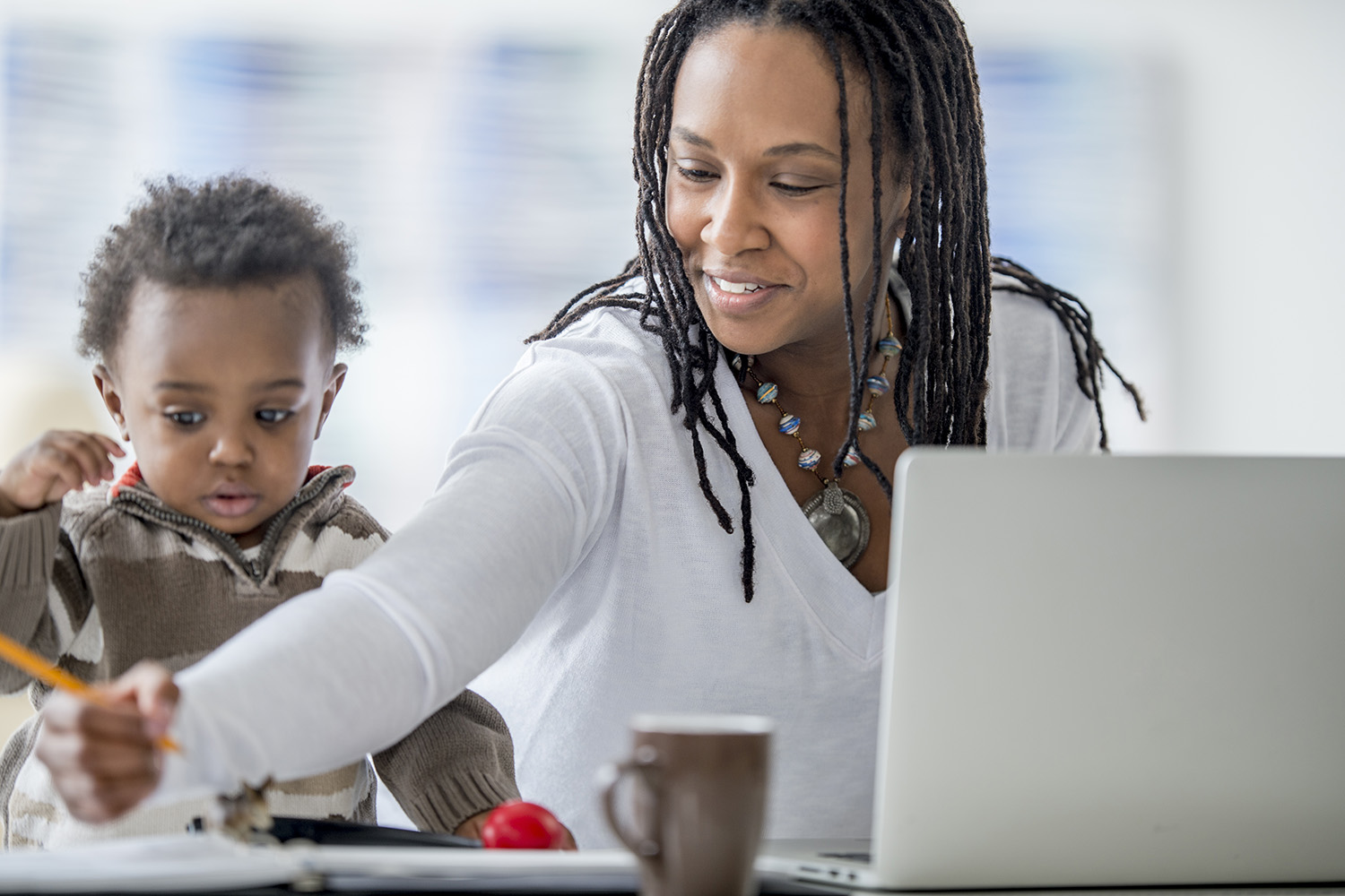 A woman of African descent and her baby boy are at home. The mother is working on a laptop computer. She is being distracted by her son, who was playing with a pencil.