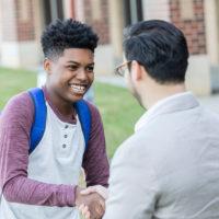 Teacher and student shake hands