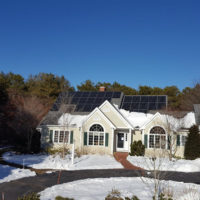 House with solar panels surrounded by snow.