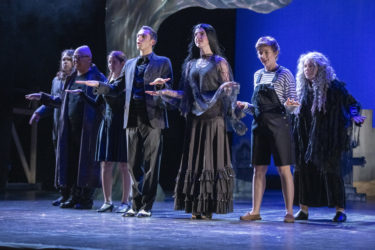 The seven members of the Addams Family sing.
