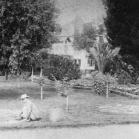 Black and white image of worker in a yard.