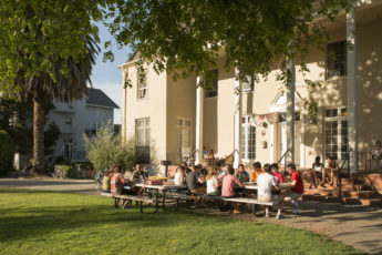 Students sitting at tables outside residence.