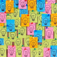 bulletin board covered with sticky notes embellished with drawings of lightbulbs representing ideas
