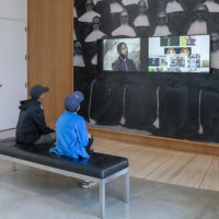 Visitors at Stanford's Cantor Arts Center absorb the video images from Kahlil Joseph's BLKNWS, 2018.