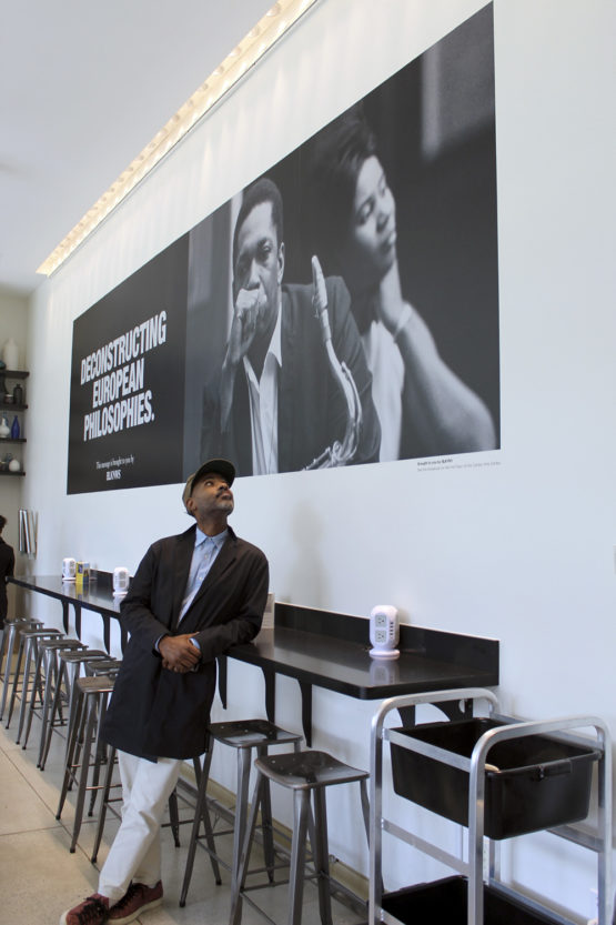 Artist Kahlil Joseph pauses in front of a BLKNWS poster in the Cantor Café.