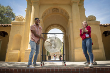 Chinemere Uche of Maumee, Ohio, rings the gong with Stanford student Sofia Dudas to celebrate his intention to attend Stanford.