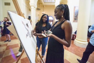 Esther Omode works on a pastel drawing in the rotunda
