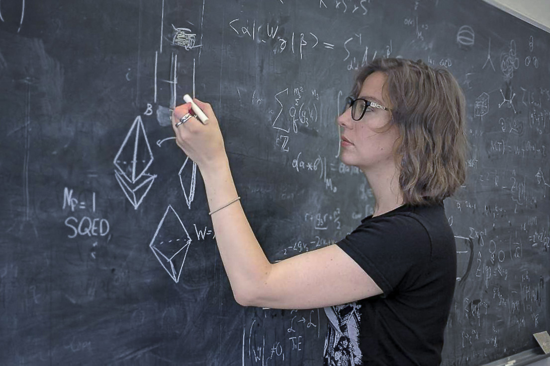 Physicist Natalie Paquette working at a chalkboard