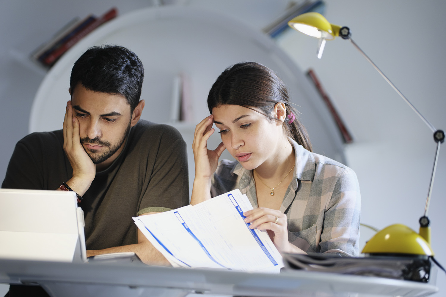 Millennial couple reviewing invoices and looking stressed