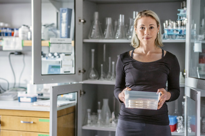 A woman stands in front of a cabinet of lab glassware.