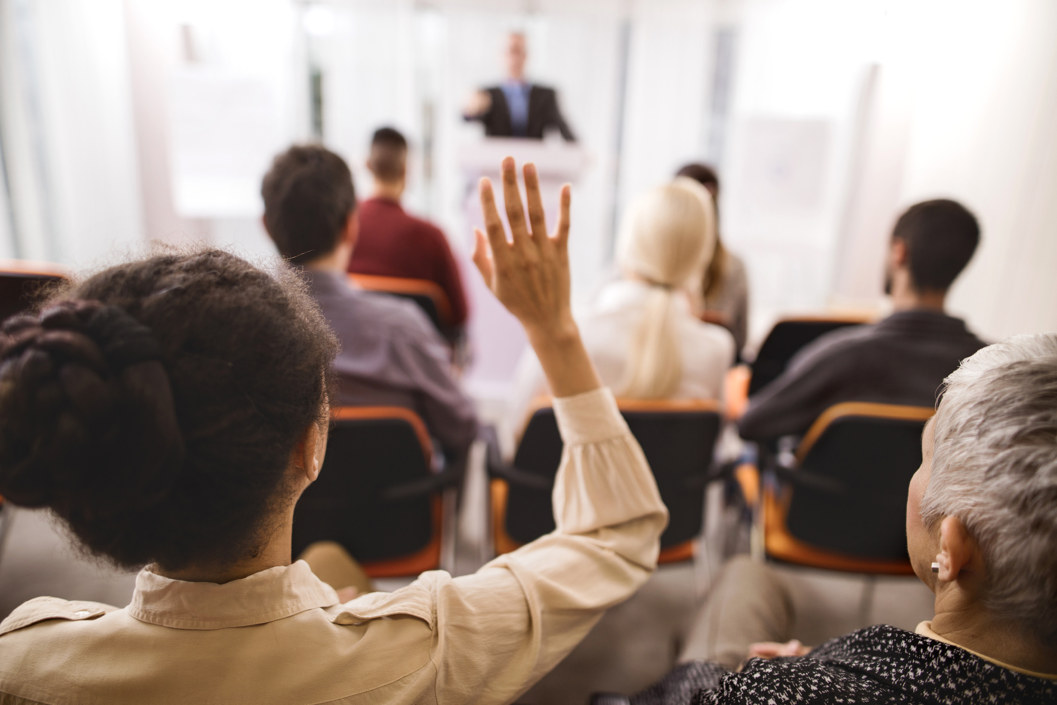 Rear view of a woman raising her hand to ask a question at a conference session.