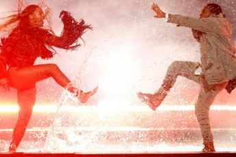 Two people dance in a puddle