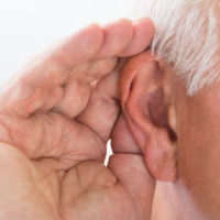 A hand cupping an ear