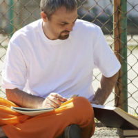 Man reading books at prison yard