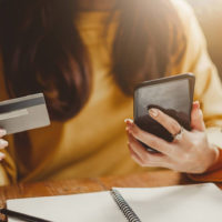 woman holding phone in one hand an credit card in the other to illustrate shopping online