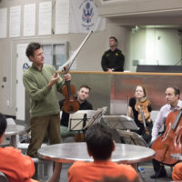 Stanford Artists-In-Residence the St. Lawrence String Quartet, play before a group of inmates at the San Francisco county jail where they performed and anwered questions about the music and their instruments. Here violinist Geoff Nuttall demonstrates the horsehair ribbon of the violin bow.