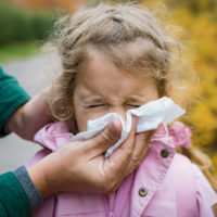 Father wiping daughter's nose with handkerchief. Sick little girl with cold and flu standing outdoors. Preschooler sneezing, coughing, having runny red nose.