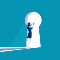 Businesswoman peers through a large keyhole.