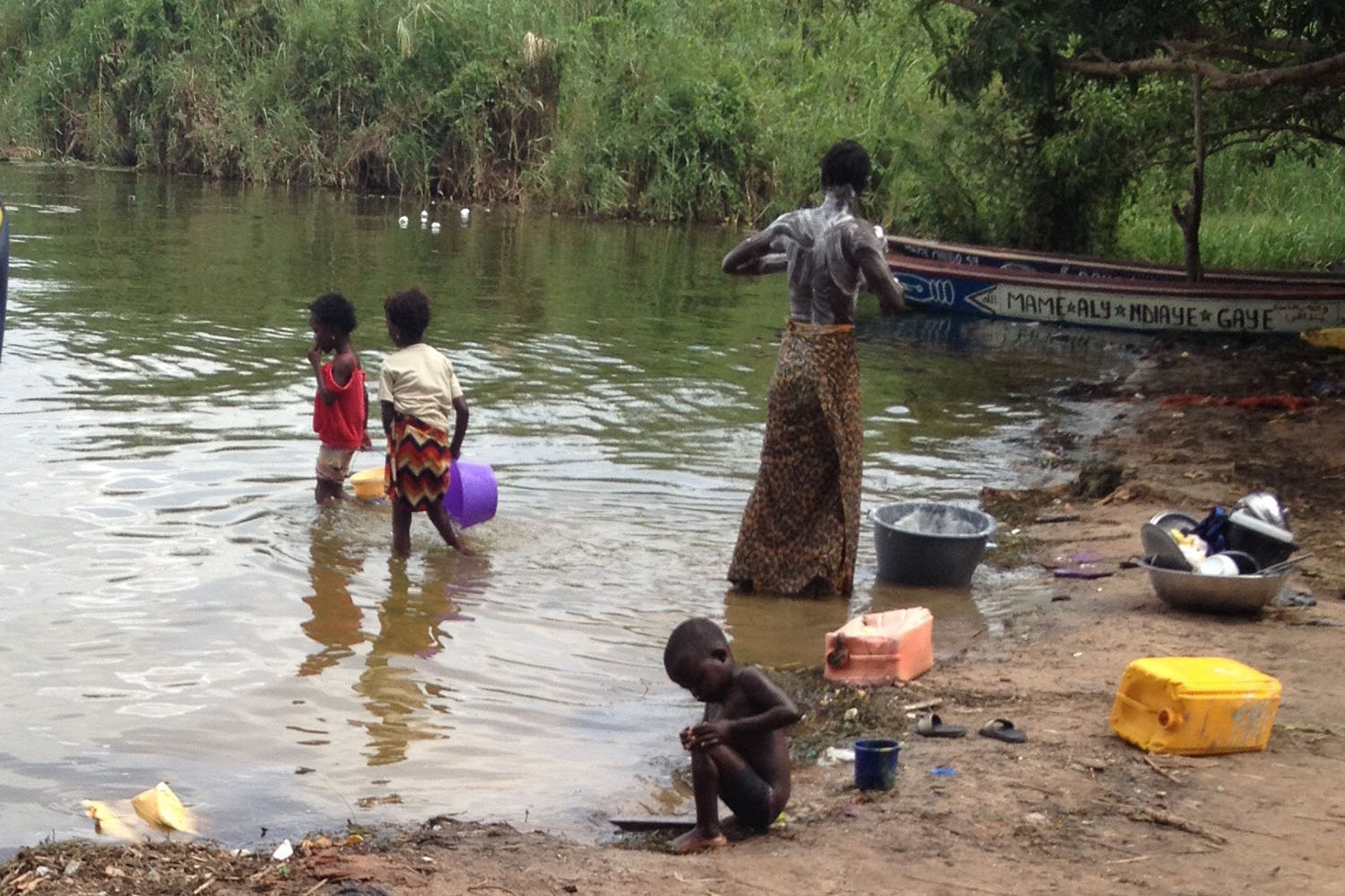 A man bathes in the Senegal River, while children play nearby.