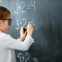Schoolgirl writing figures on blackboard