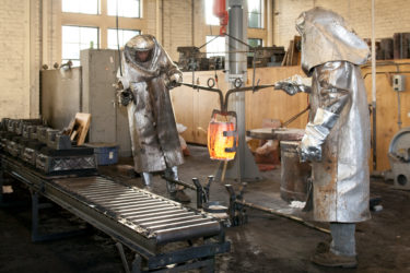 Two people in full-body protective gear moving a container of molten metal toward molds