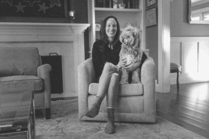 Amy Zegart smiling, sitting in a chair with her dog, whose head is cocked to the side