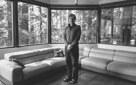 Chris Chafe standing in a room surrounded by windows with views of redwood trees