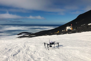 A drone on snow with a small building in the background and water in the distance