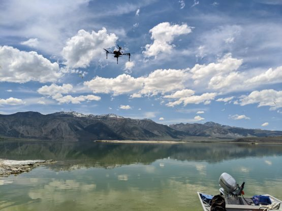 Drone hovers over the water with a mountain range in the background and the back of a motorboat in the foreground