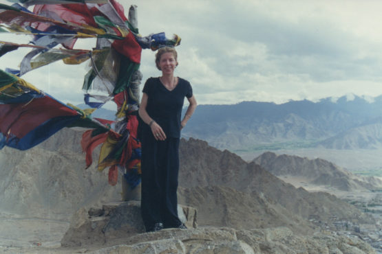 Anna Bigelow in Ladakh, India with Buddhist prayer flags in the background