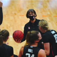 Tara VanDerveer holding a basketball with players around her