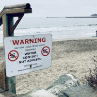 A beach in Half Moon Bay, California, displays a public health warning due to the detection of high concentrations of bacteria in the water.