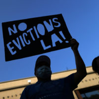 protestor with sign against evictions