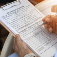 closeup of person filling out health insurance claim form