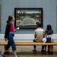 people in an art museum looking at paintings