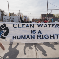 Students walking down a street, holding a banner that says Clean Water is a Human Right
