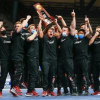 Cheering men holding trophy