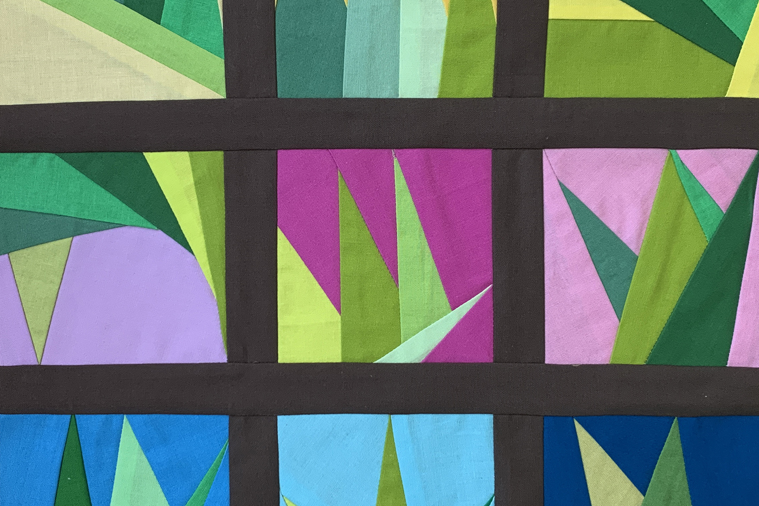 A quilting pattern with several green triangles in different square panels